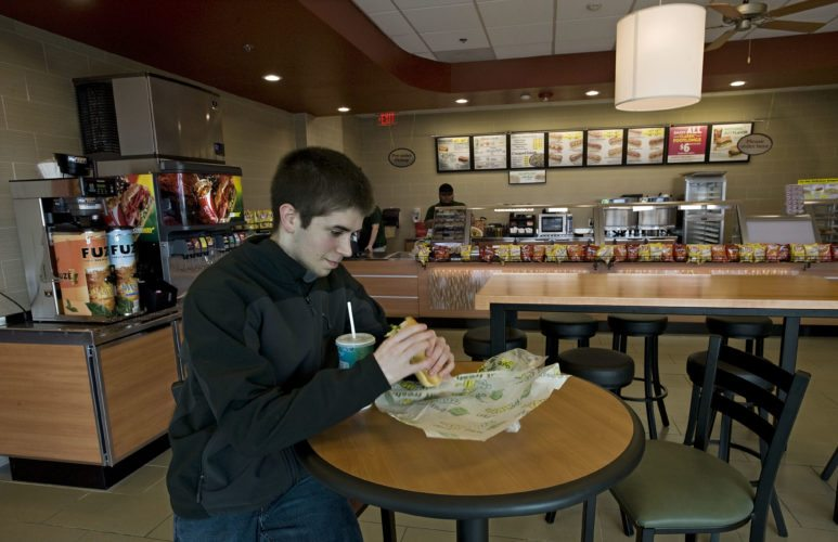 Cameron Bowers, 19, of Winchester, eats a sandwich inside the new Subway at Lord Fairfax Community College on Wednesday.  Rich Cooley/Daily